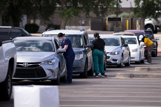 People wait in their cars to be tested for COVID-19 on July 2, 2020, at South Mountain Community College in Phoenix.