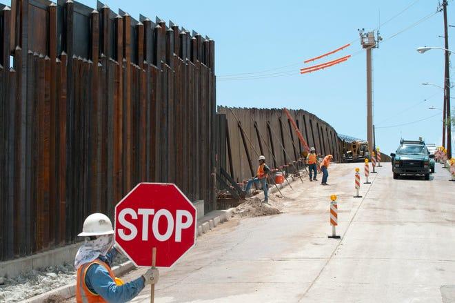 Fotografía de archivo de unos trabajadores finalizan un trozo del muro fronterizo que separa México de Estados Unidos en el paso de Deconcini en Nogales (Arizona).