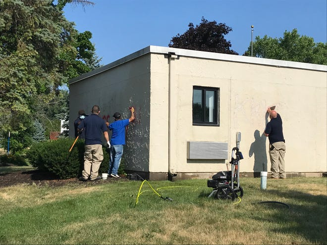 Workers remove hateful graffiti spray painted on the rental office at the Pines of Perinton on July 2, 2020.
