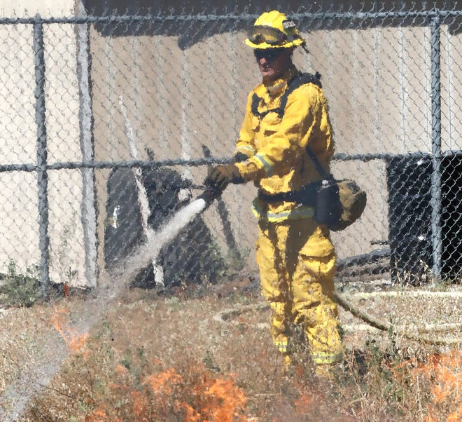 Redding firefighter Scott Kindy extinguishes a grass fire after fire officials lit fireworks in a demonstration Thursday, July 2, 2020, to remind residents that all fireworks are illegal in Shasta County.