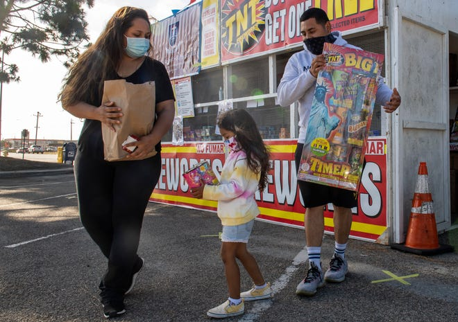 Each member of the Vasquez family carries fireworks purchased from a TNT Fireworks stand to support Sacred Heart School in Salinas, Calif., on Tuesday, June 30, 2020.