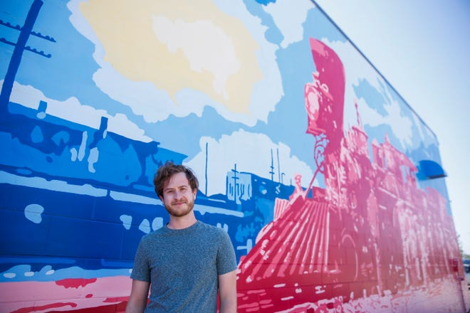Artist Zach DeBoer poses for a portrait in front of his mural on Thursday, July 2, 2020 at Monk's in Sioux Falls, S.D.