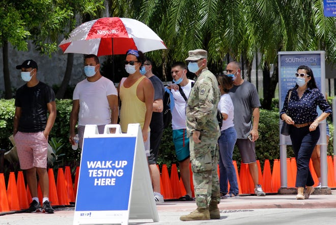 People wait in line at a walk-up testing site for COVID-19 during the new coronavirus pandemic, Tuesday, June 30, 2020, in Miami Beach, Fla. (AP Photo/Lynne Sladky)