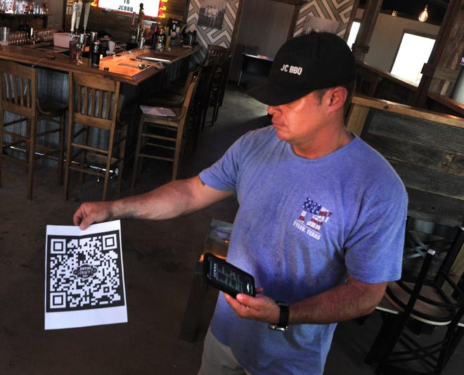 JC BBQ Co-owner, Hayden Price demonstrates how his hands-off menu system works. Price said his family-friendly business's motto is safety first and has implemented several COVID-19 protocols for keeping his patrons safe during the outbreak.