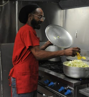 Dwayne Parker, owner of Tapa's Caribbean Kitchen, prepares food in the kitchen. Parker, from the island of Antugua, recently opened the restaurant in downtown Zanesville.