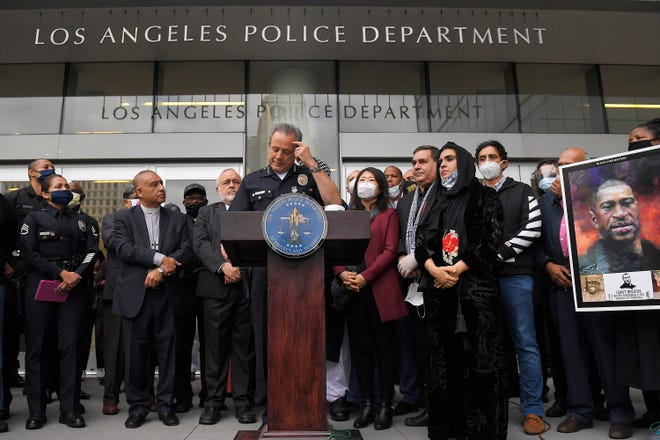 Los Angeles police chief Michel Moore, left, speaks as someone holds up a portrait of George Floyd during a vigil with members of professional associations and the interfaith community at Los Angeles Police Department headquarters, Friday, June 5, 2020, in Los Angeles.