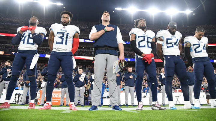 Tennessee Titans head coach Mike Vrabel and players stand during the National Anthem before the NFL Divisional Playoff game against the Baltimore Ravens at M&T Bank Stadium Saturday, Jan. 11, 2020 in Baltimore, Md.