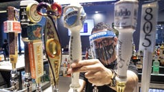 A bartender pours a beer while wearing a mask and face shield on Wednesday at Slater's 50/50 in Santa Clarita, Calif.