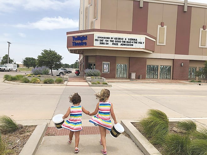 Sisters Eisley and Wren Neuhold make their way to the Twilight Theatre for the free kids summer film series in Greensburg.