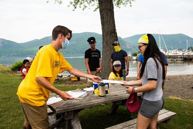 Guide Sean Coleman hands out waivers to kayakers Friday during a Storm King Adventure Tour in Cornwall-on-Hudson.