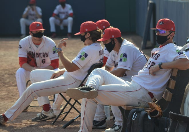 Following league safety guidelines due to the coronavirus pandemic, the Battle Creek Bombers pitchers wear masks while they sit in the bullpen Thursday during the season opener at Homer Stryker Field in Kalamazoo.