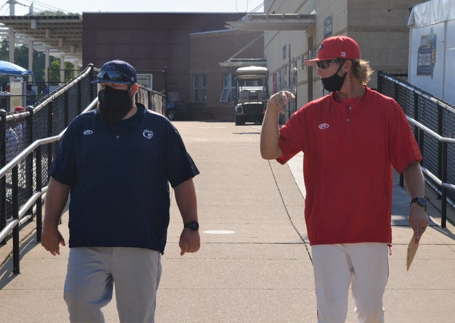 Battle Creek Bombers manager Mike Ruppenthal, right, and Kalamazoo Growlers manager Cody Piechocki wear masks as they leave the locker rooms and head to the field prior to the season opener.