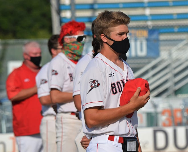 Battle Creek's Josh Swinehart, stands apart from teammates, following social distance rules, and wears a mask during the pregame playing of the national anthem on the Bombers season opener on Thursday at Kalamazoo's Homer Stryker Field.
