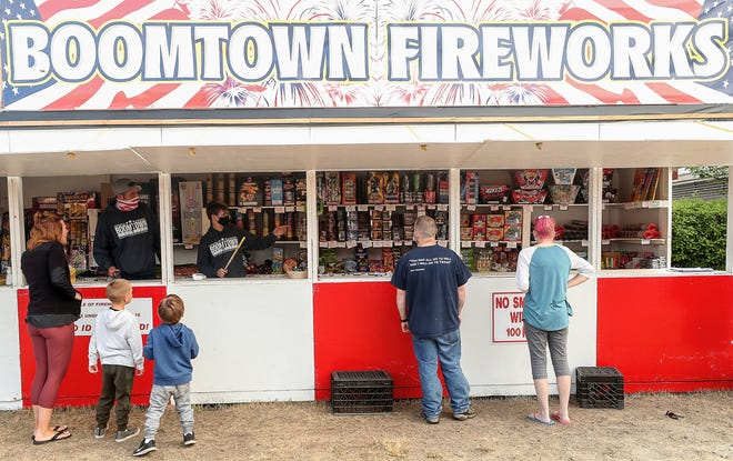 David Scott, left, and Dakota Williams help customers from behind the counter at the Boomtown Fireworks stand on Wheaton Way on Thursday.