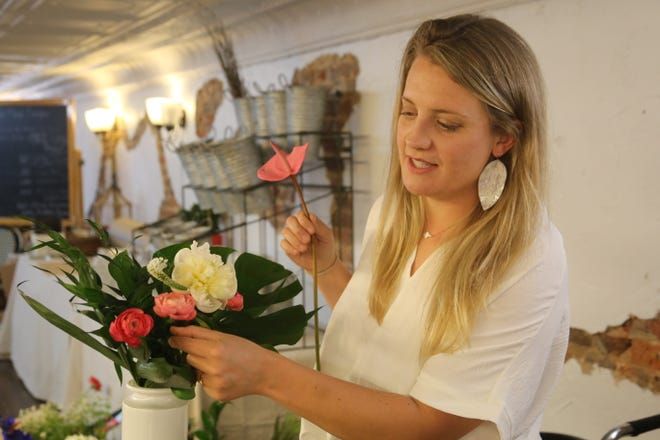 Kassie Peterson of Kassie Kay Floral Designs works on a floral arrangement in her shop inside Mildred & Mable's on Franklin Street in downtown Clarksville on July 2, 2020.