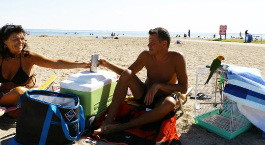 Gigi Canale, 59, of Warren, left, and Steven Smith, 50, of Warren relax on Lake St. Clair Metropark Beach in Harrison Charter Township on July 1, 2020.