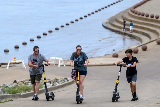 Ann Calvert, center, laughs as she gets her e-scooter to work while Jerad Shockley, left, and Baker Calvert, 14, have to push their e-scooters up the large hill at Dress Plaza in Evansville, Ind., Friday, July 3, 2020. They traveled to the riverfront to try out the e-scooters, which can be found and rented on a smartphone app called Evil Corn Dogs.