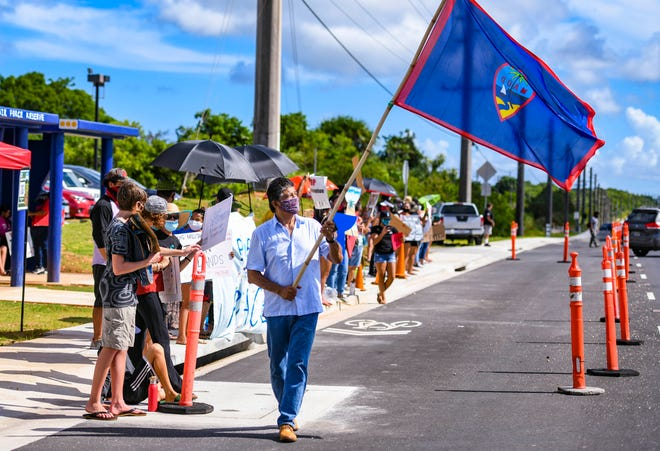 Yigo Mayor Rudy Matanane, foreground, raises a Guam flag high as he and dozens of island shareholders conduct a peaceful protest near the entrance to the Naval Computer and Telecommunications Station Guam, along Route 3 in Dededo, in this July 3 file photo.