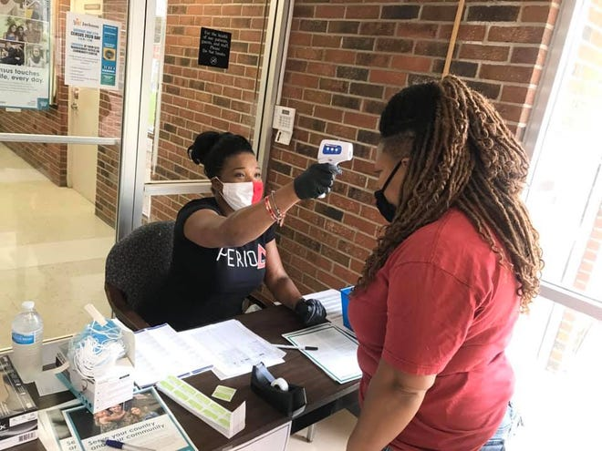 Elverna Cain, a member of Delta Sigma Theta Sorority, Inc., checks Teresa Vincent's temperature at a census drive at Lincoln Courts on Sat., June 27, 2020.