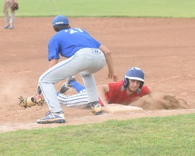 MacLeod's Logan Ballard dives safely back into first base at Harrison on Thursday.