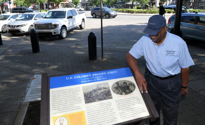 Hewitt Sawyers stands with a colored troops marker that he helped get installed in front of the Williamson County historic courthouse in downtown Franklin on Friday, July 3, 2020.