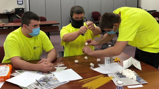 Donavin Brooks, Cameron Carter and Daniel Hunt make a tower out of marshmallows and spaghetti Thursday at Licking County Ohio Means Jobs during a team building exercise. Recent high school graduates are preparing to work local manufacturing jobs this summer.