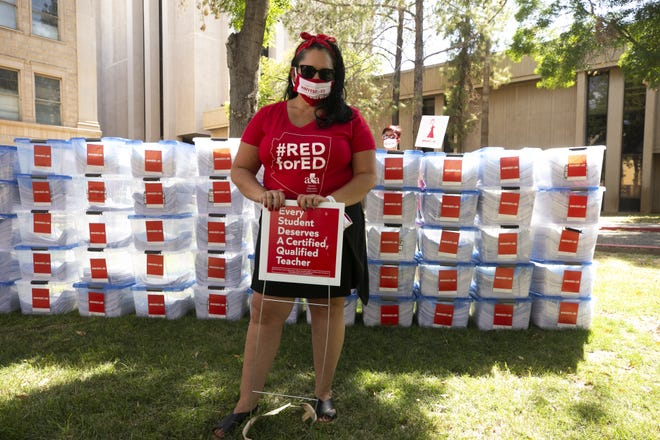 Marisol Garcia, an eighth-grade social studies teacher in the Isaac School District and vice president of the Arizona Education Association, stands by boxes containing the 435,669 signatures for the InvestInEd ballot initiative that were turned in at the Arizona Secretary of State's Office at the state Capitol in Phoenix on July 2, 2020.