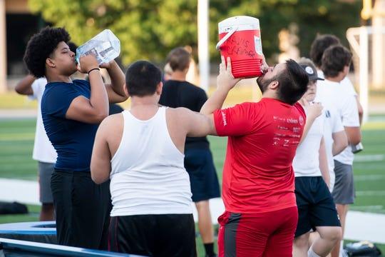 Chambersburg Area Senior High School student-athletes take a water break during a summer football workout at Trojan Stadium on Thursday.