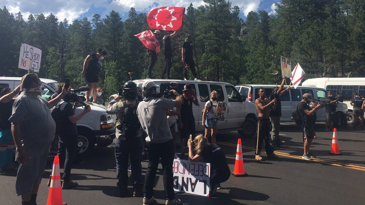 Protesters block Highway 16A outside of Keystone ahead of President Donald Trump's arrival in the Black Hills for the Mount Rushmore fireworks display.