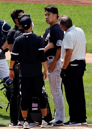 Yankees pitcher Masahiro Tanaka is tended to by team medical personnel after being hit by a ball off the bat of Yankees Giancarlo Stanton during a baseball a workout at Yankee Stadium. (AP Photo/Adam Hunger)