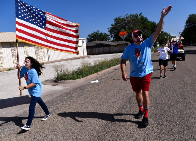 Alan Clute waves and he and Melissa McClung lead a small procession through the Hillcrest neighborhood Saturday. While the official neighborhood Independence Day parade was canceled due to COVID-19 concerns, a reduced group met to celebrate the holiday with social distancing and masks.