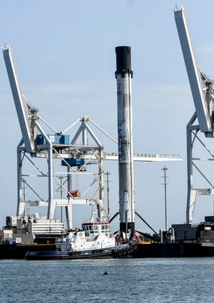 A SpaceX booster is brought into Port Canaveral on July 4 aboard the drone ship Just Read the Instructions.