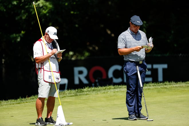 """Bryson DeChambeau checks his """"green-reading book"""" at the Detroit Golf Cub last year during the Rocket Mortgage Classic. The books may be banned on the PGA Tour after a vote by the Player Advisory Council."""