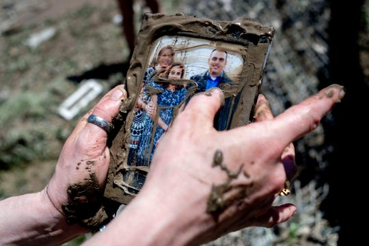 Sanford resident Kendra Tucker wipes away muck May 21 after finding a family photo for her aunt and uncle after their home was washed away in flood waters, in Sanford,