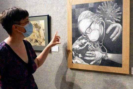 """Kate Oman, Bonifas gallery coordinator, describes Escanaba artist Brian Burroughs' artwork, """"Essential"""" in the Bonifas gallery, June 25, 2020, in Escanaba."""