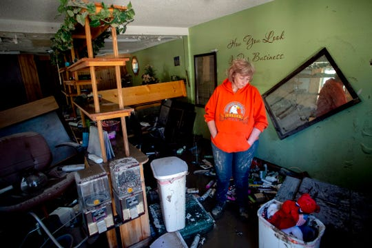Sanford resident Connie Methner, owner of CJ's Hairstyling, bows her head May 21 as she copes with the damage after water flooded her salon to its ceiling in Sanford.