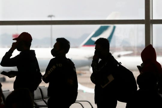 People wearing masks line up for departure Feb. 4 at Hong Kong airport.