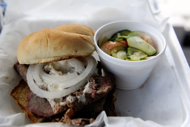 An O'George sandwich with sliced smoked sirloin, horseradish and onion and homemade cucumber salad from the Pappa Bear's Catering truck on Thursday, June 18, 2020.