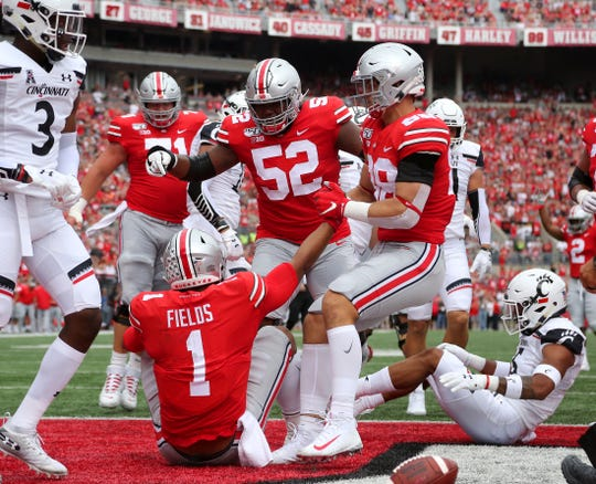 Ohio State guard Wyatt Davis (52), here congratulating quarterback Justin Fields for scoring a touchdown against Cincinnati, is an All-American in everybody's book.