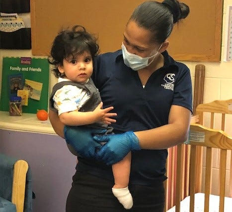 A United Community Center staff member holds a toddler while wearing a mask and gloves.