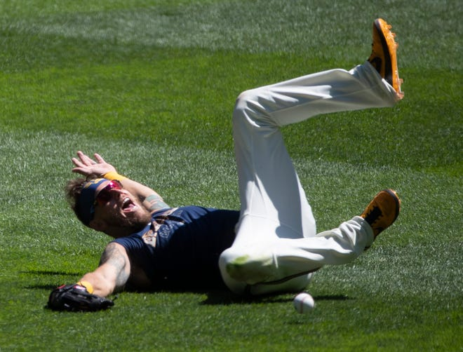 Logan Morrison tries to make a diving catch during a Brewers' summer camp practice. The versatile veteran is trying to make the roster for the shortened season.