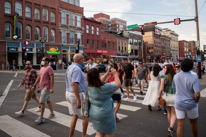 People walk along Lower Broadway in Nashville on July 3.