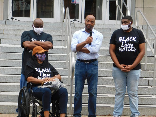 Daryl Washington, a Dallas lawyer, speaks outside the St. Landry Parish Courthouse. Washington represents Jonah Coleman, right,  who authorities said was beaten by a white Opelousas police officer while hospitalized.  Coleman's parents, left, attended the rally Friday night.