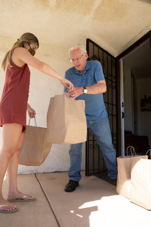 Malia Botello, left, of Wally's Desert Turtle delivers meals to Ray Werner and his wife as part of the Great Plates Delivered program administered by the city of Rancho Mirage, Calif., on Saturday, July 3. 2020. The state has extended the program through June 7.