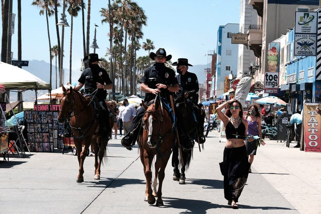 """Los Angeles Police officers on horseback patrol the strand along Venice Beach on Friday, July 3, 2020, in Los Angeles. In addition to local law enforcement authorities in some areas taking steps to enforce public health orders, Gov. Gavin Newsom dispatched """"strike teams"""" to help ensure compliance at businesses across the state."""