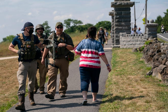 Members of a militia walk past a tourist as they patrol the area surrounding the Gettysburg National Cemetery Saturday, July 4, 2020, at Gettysburg National Military Park, in Gettysburg, Pa. (AP Photo/Carolyn Kaster)