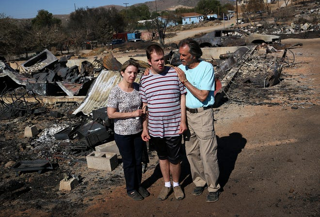 John Range, right, stands with his wife Nancy and son Brogan at the site of their home that burned during the Poeville Fire near Reno on July 3, 2020.