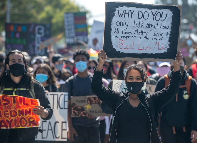 "A woman leads the march as she holds a sign that reads, ""Why do you only talk about how 'All Lives Matter' when it's a response to the cry of Black Lives Matter?"" during the  Monterey County Black & Brown Solidarity Coalition march in Salinas, Calif., on Friday, July 3, 2020."