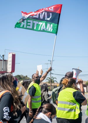Pastor A.L. Smith, leads the march as he holds a Black Lives Matter flag during the Monterey County Black & Brown Solidarity Coalition march in Salinas, Calif., on Friday, July 3, 2020.