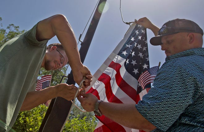 Derrick Rindeikis, left, and Caleb Wallace, right, raise an American flag in front of the Tom Green County courthouse during a rally Saturday, July 4, 2020.